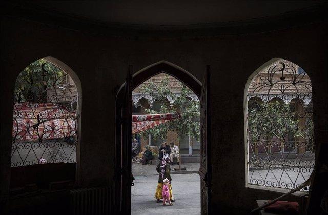 Una mujer uigur pasea en Kashgar, Xinjiang