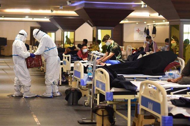 Trabajadores sanitarios atienden a pacientes con coronavirus en un centro de cuarentena en Nueva Delhi