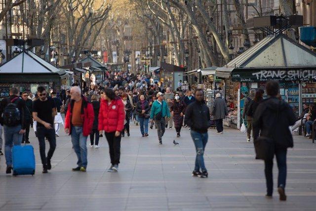 Varias personas caminan por las Ramblas de Barcelona, ciudad en la que, a pesar de haberse reducido, el turismo no ha caído tanto como en Madrid, donde los efectos del coronavirus han sido más letales, en Barcelona (Catalunya, España), a 13 de marzo de 20