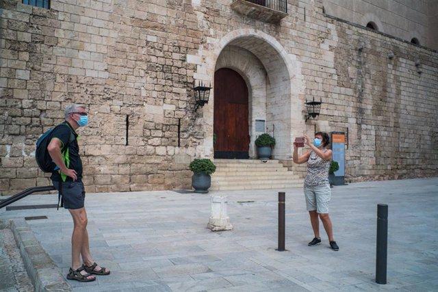 Dos turistas hacen una foto junto a la Almudaina
