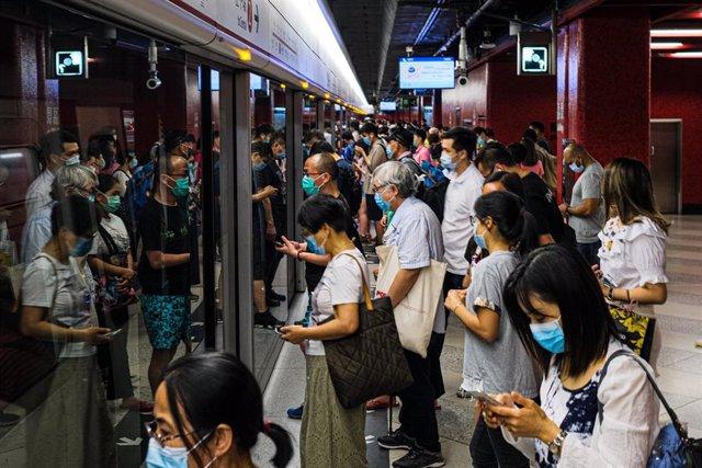 Usuarios del metro esperan para subirse a un vagón en Hoong Kong.