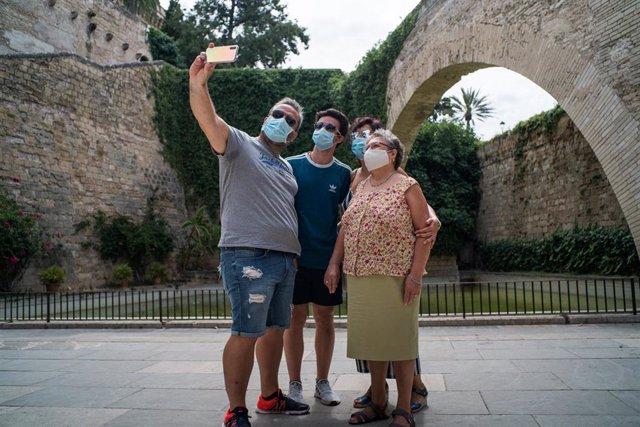 Varios turistas se hacen una foto junto a los Jardines de S'Hort del Rei de Palma de Mallorca durante el primer día de uso obligatorio de la mascarilla en Baleares por el Covid-19, en Palma de Mallorca, Islas Baleares (España) a 13 de julio de 2020.