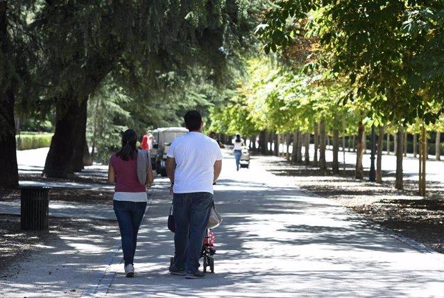 Una pareja pasea con su bebé en un carrito por un parque de Madrid.