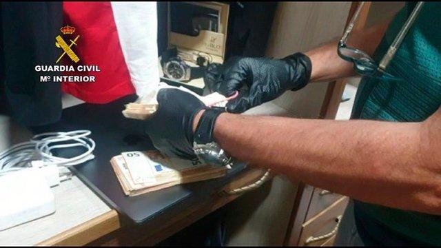 Un agnte contando dinero tras uno de los registros de la operación por blanqueo de capitales