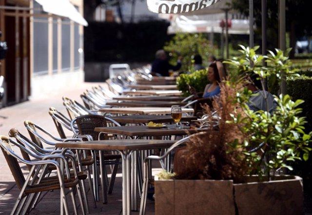 Varias personas disfrutan en una terraza. Archivo