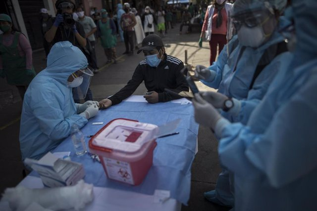 Un trabajador sanitario toma muestras en Lima, Perú.