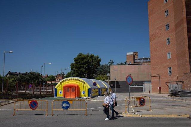 Dos personas pasan cerca del Hospital de campaña de Lleida