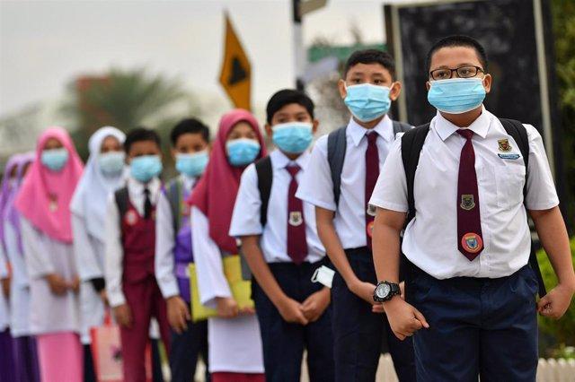 Alumnos de un colegio de la localidad malasia de Ipoh hacen cola paa que les tomen la temperatura