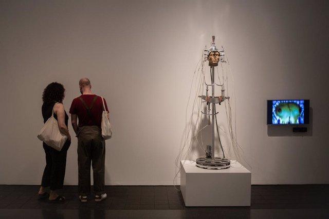 Dos personas observan las obras de la exposición 'Acció. Una història provisional dels noranta' disponibles en el Museu d'Art Contemporani de Barcelona (MACBA).