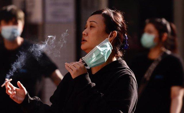 Una mujer se quita la mascarilla para fumar durante la pandemia de coronavirus en Hong Kong