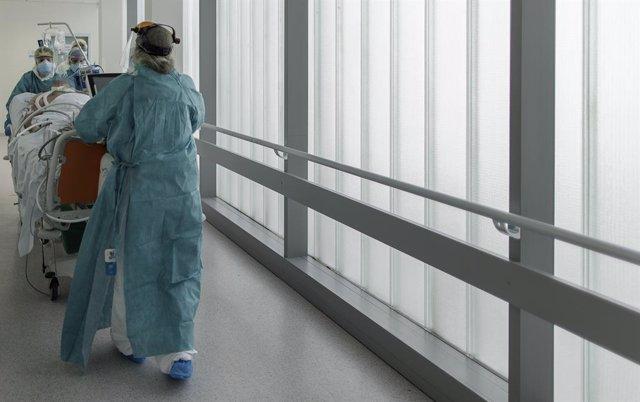 Personal sanitari totalment protegit traslladen un pacient ingressat a la unitat de vigilància intensiva (Arxiu)