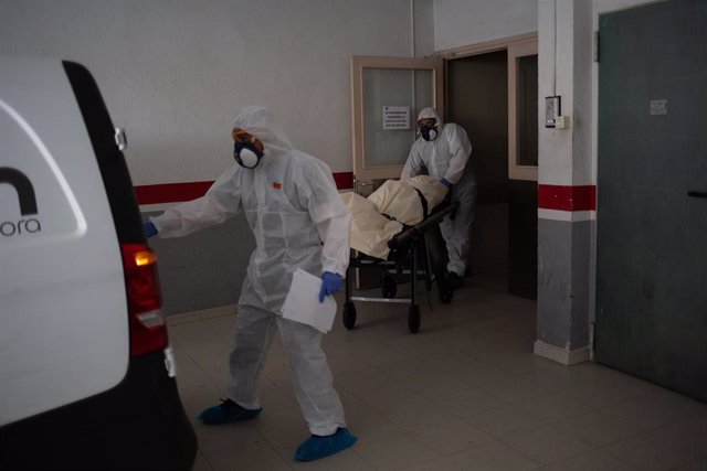 Varios operarios protegidos de los Servicios Funerarios Memora trasladan un cuerpo de una residencia  en el garaje de una residencia de ancianos