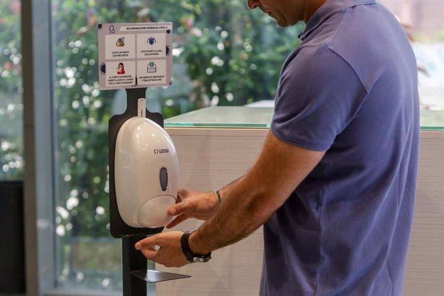 Un trabajador se desinfecta las manos