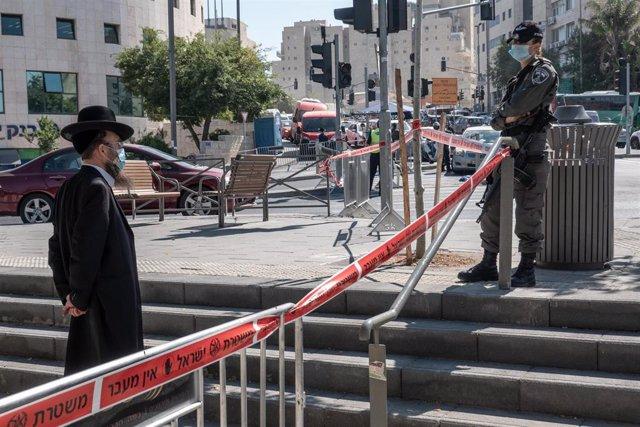 Un policía de Israel junto a un hombre en Jerusalén durante la pandemia de coronavirus