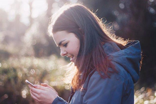 Chica con un móvil en el campo