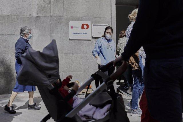 Mujeres esperan en las inmediaciones de la Parroquia Santa María Micaela y San Enrique para recibir ayuda de la Fundación Madrina. En Madrid, (España), a 12 de junio de 2020.
