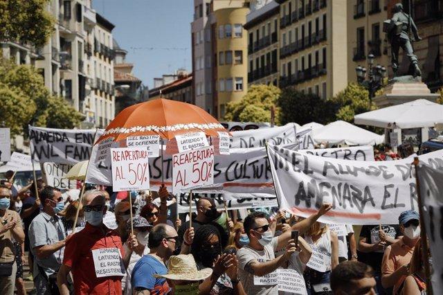 """Una multitud de personas con carteles y pancartas se concentra para denunciar que El Rastro está """"amenazado"""" bajo el lema 'Por la reapertura ya del Rastro de Madrid respetando a todos y cada uno de los titulares de los puestos de venta'."""