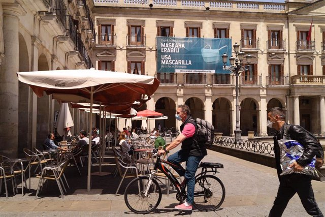 Un hombre con mascarilla pasea en bicicleta al lado de una terraza de una céntrica calle de Vitoria-Gasteiz, Álava