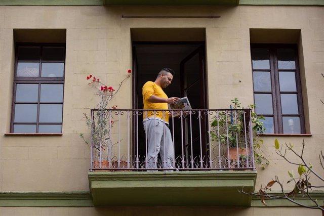 Un hombre lee un libro en el balcón de su casa con ocasión de la Diada de Sant Jordi de 2020 marcada por el coronavirus (Archivo)
