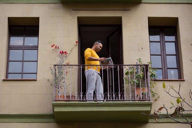 Un home llegeix un llibre al balcó de casa seva durant la Diada de Sant Jordi del 2020.