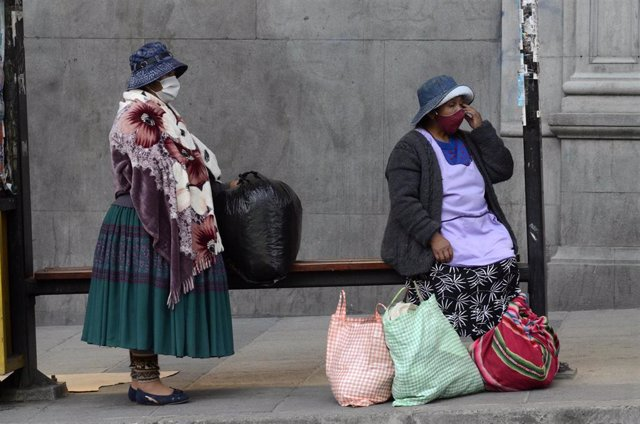 01 June 2020, Bolivia, La Paz: Two women with face masks wait for the bus at a bus stop amid the relaxations of restrictions that were put into effect to curb the spreading of coronavirus. Photo: Alexis-Demarco/ABI/dpa