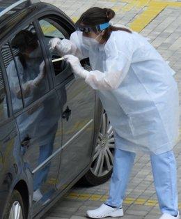Una trabajadoras del Hospital de Eibar realiza test PCR al conductor de un vehículo en el parking del centro.