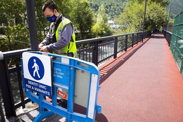 Un operari del Comú d'Andorra la Vella reforçant la senyalització per establir un únic sentit de circulació per als vianants pel costat del riu.