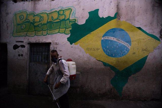 Un hombre desinfecta una favela por el coronavirus en Sao Paulo.