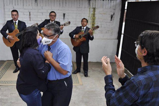 Dos personas bailando con mascarilla por el coronavirus en Quito, Ecuador.