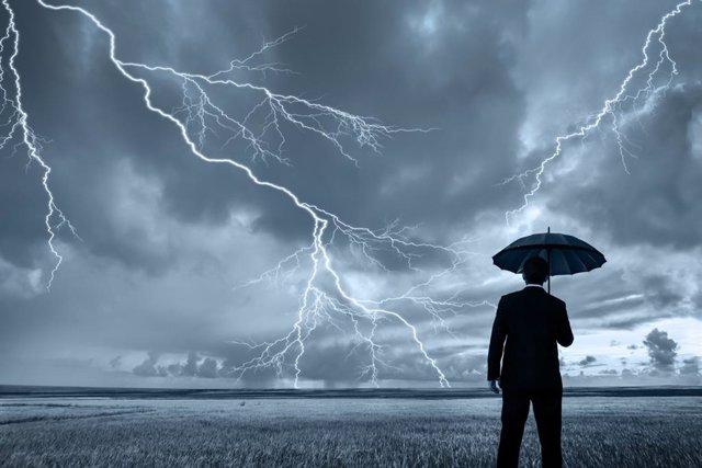 Un hombre con paraguas bajo la tormenta mientras caen los rayos.