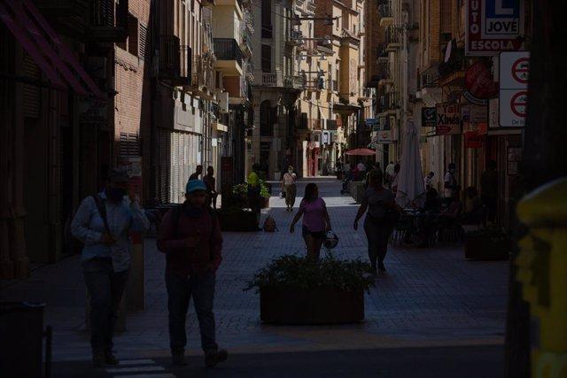 Diverses persones caminen per un carrer del centre de Lleida, capital de la comarca del Segrià