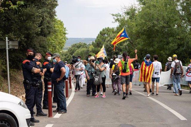 Agents dels Mossos d'Esquadra observen els manifestants que protesten contra la visita del rei al Reial Monestir de Santa Maria de Poblet (Tarragona)