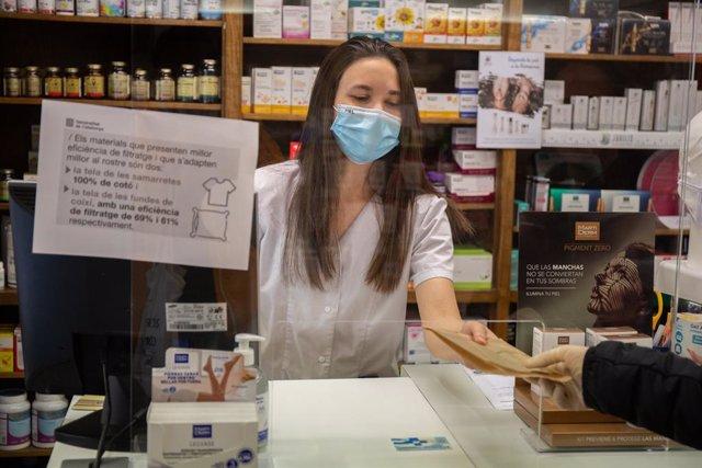 Una farmacèutica amb un paquet de mascaretes