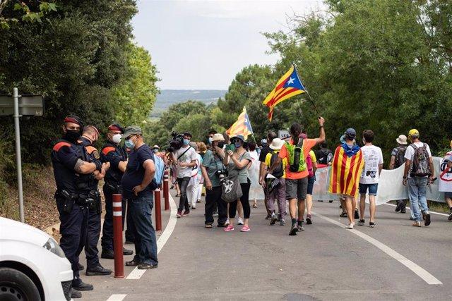 Agentes de los Mossos d'Esquadra observan a los manifestantes que protestan contra la visita del Rey en el Monasterio de Santa María de Poblet (Tarragona)