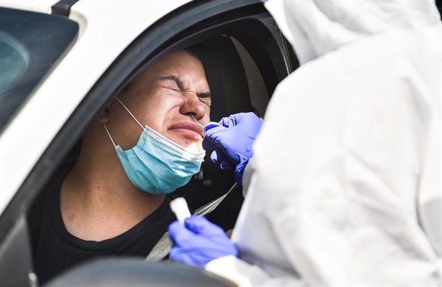 17 July 2020, US, Rock Island: A health worker takes a swab from a man in his car for coronavirus PCR tests at a coronavirus testing mobile facility in the parking lot of the QCCA Expo Center. Photo: Meg Mclaughlin/Dispatch Argus via ZUMA Wire/dpa