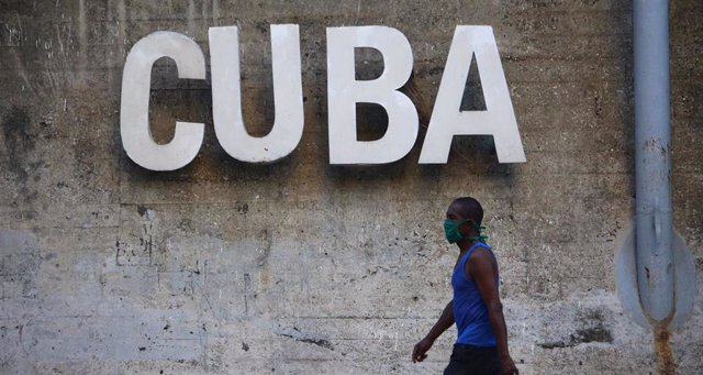 30 April 2020, Cuba, Havana: A man wearing a face mask walks past a sign reading 'CUBA'. Labour Day Parade has been cancelled in Cuba amid the coronavirus pandemic. Photo: Guillermo Nova/dpa