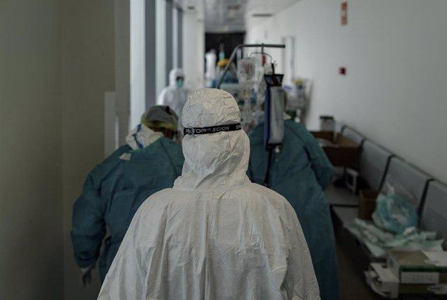 Personal sanitari totalment protegit traslla un pacient ingressat a la unitat de vigilància intensiva (arxiu)
