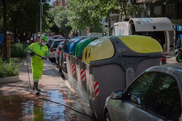 Un operario de limpieza del servicio municipal desinfectando un contenedor amarillo de basura