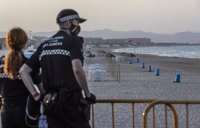 Dos policías locales contemplan la playa de la Malvarrosa durante la noche de San Juan en Valencia (archivo)