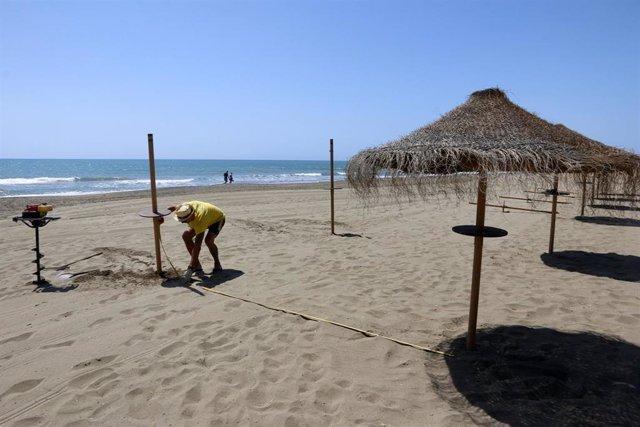Un trabajador del chiringuito María, ubicado en  la playa de Sacaba en la barriada de Huelín, realiza mediciones de colocación de las sombrillas para  la reapertura