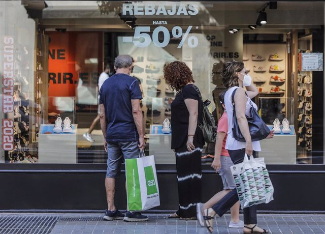 Varias personas observan objetivos del escaparate de una tienda con carteles indicativos de rebajas en Valencia