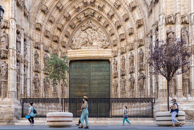 Paseantes por la puerta de la Anunciación de la Catedral de Sevilla