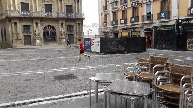 Una persona corriendo en la plaza del Ayuntamiento de Pamplona en el primer día en que se permite hacer ejercicio al aire libre