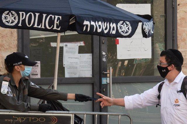 Una policía de Israel habla con un hombre en Jerusalén durante la pandemia de coronavirus