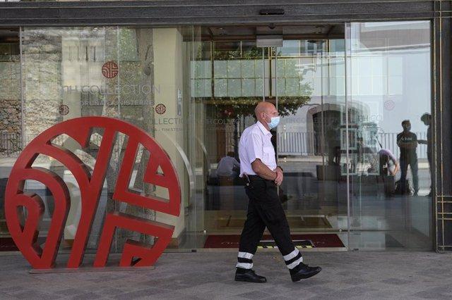 Un trabajador de seguridad camina cerca de la puerta del hotel NH Finisterre de A Coruña donde los jugadores del CF Fuenlabrada permanecen confinados en él tras haber dado positivo en coronavirus varios de sus miembros
