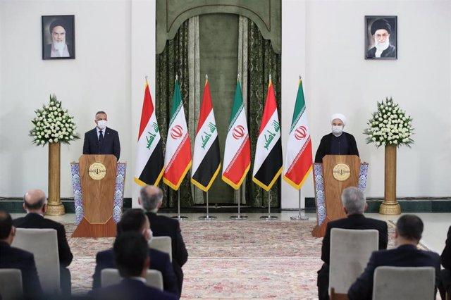 El primer ministro de Irak, Mostafá al Kazemi (i), junto al presidente de Irán, Hasán Rohani (d), durante su visita a Irán