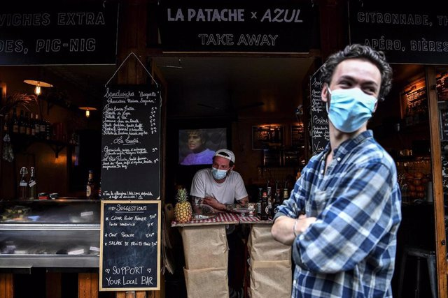 Trabajadores de un bar con mascarillas en Francia.