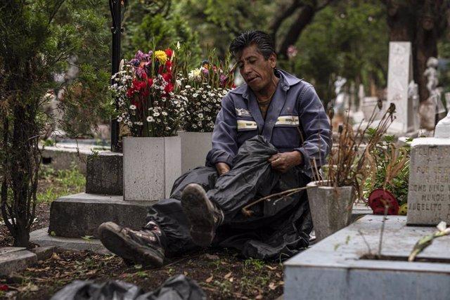 Un empleado de un cementerio en ciudad de México se dispone a enterrar a una persona que ha fallecido a causa de la COVID-19.