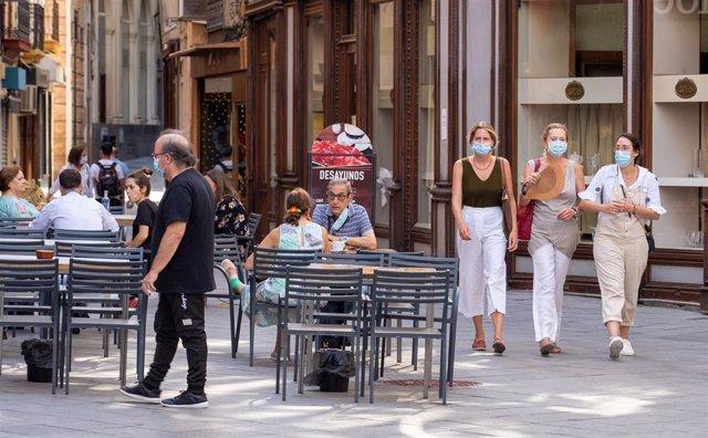 Tres ciudadanas pasean con mascarillas y abanico por el fuerte calor en el primer día de uso obligatorio de mascarillas en Sevilla