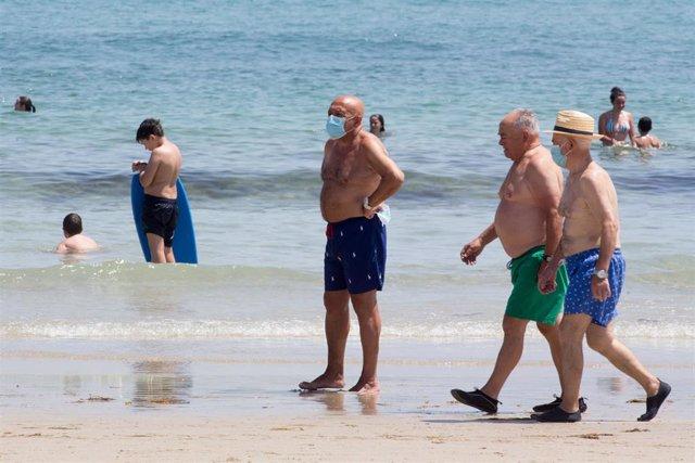 Tres hombres protegidos con mascarillas pasean por la Playa de A Rapadoira en Foz, en la comarca de A Mariña, Lugo, Galicia (España), a 9 de julio de 2020.